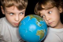 Menino e menina que olham steadfastly o globo Imagem de Stock