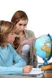 Menino e menina que olham um globo imagem de stock