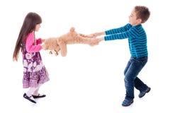 Menino e menina que puxam o urso do brinquedo Fotografia de Stock