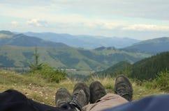 Menino e menina que relaxam sob o sol Homem e mulher que encontram-se no fundo, em montanhas da neve e em nuvens bonitos sunbed e Imagem de Stock