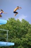 Menino e menina que saltam do trampolim Imagem de Stock