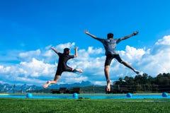 Menino e menina que saltam na associação no lago Fotos de Stock