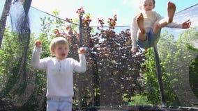 Menino e menina que saltam no trampolim no quintal da casa Tiro do movimento lento filme