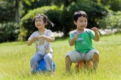 Menino e menina que sentam-se na esfera Foto de Stock Royalty Free