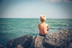 Menino e menina que sentam-se na pedra no mar Imagem de Stock Royalty Free