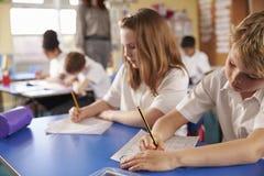 Menino e menina que trabalham na classe de escola primária, fim acima Imagem de Stock