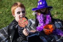Menino e menina que vestem o traje do Dia das Bruxas com doces esqueleto bruxa foto de stock