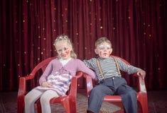 Menino e menina vestidos como os palhaços que sentam-se em cadeiras Fotos de Stock