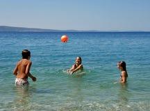 Menino e meninas com uma esfera no mar Fotografia de Stock Royalty Free