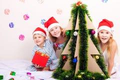 Menino e meninas de sorriso pequenos felizes com chapéu do Natal Foto de Stock