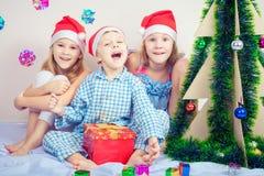 Menino e meninas de sorriso pequenos felizes com chapéu do Natal Fotos de Stock