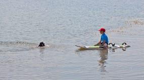Menino e meninas que sentam-se na mesa surfando e no olhar no mar azul Fotos de Stock Royalty Free