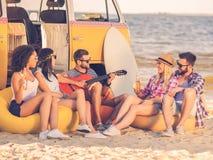 Menino e meninas que sentam-se na mesa surfando e no olhar no mar azul Imagem de Stock Royalty Free