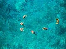 Menino e meninas que sentam-se na mesa surfando e no olhar no mar azul Imagens de Stock