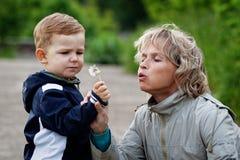 Menino e mulher com dente-de-leão Imagem de Stock