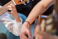 Menino e mulher que jogam a guitarra imagem de stock