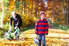 Menino e pai da criança com a bicicleta na floresta do outono Fotografia de Stock