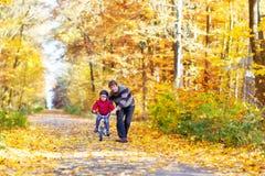 Menino e pai da criança com a bicicleta na floresta do outono Fotos de Stock Royalty Free