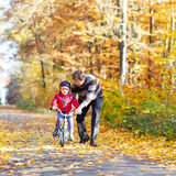 Menino e pai da criança com a bicicleta na floresta do outono Imagens de Stock Royalty Free