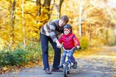 Menino e pai da criança com a bicicleta na floresta do outono Imagens de Stock