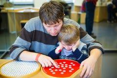 Menino e pai da criança que jogam com jogo da lógica Foto de Stock Royalty Free