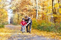Menino e pai da criança com a bicicleta no outono Fotografia de Stock