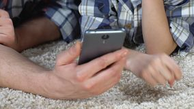 Menino e pai de escola que jogam o jogo no smartphone em casa, tendo o divertimento, família filme