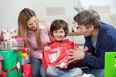 Menino e pais que abrem o presente de Natal Foto de Stock
