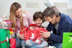 Menino e pais que abrem o presente de Natal Foto de Stock Royalty Free