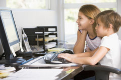 Menino e rapariga novos no escritório com computador Imagem de Stock