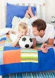 Menino e seu pai que prestam atenção a um fósforo de futebol Fotografia de Stock