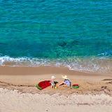 Menino e sua mãe na praia com flutuador inflável fotos de stock royalty free