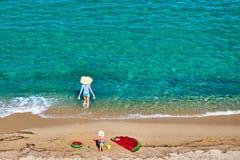 Menino e sua mãe na praia com flutuador inflável foto de stock royalty free