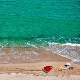 Menino e sua mãe na praia com flutuador inflável imagem de stock royalty free