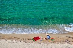 Menino e sua m?e na praia com flutuador infl?vel imagem de stock