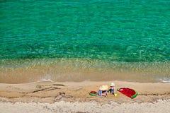 Menino e sua m?e na praia com flutuador infl?vel fotografia de stock royalty free