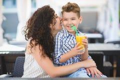 Menino e sua sobremesa do gosto da mãe com suco no restaurante do recurso exterior imagem de stock royalty free
