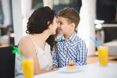 Menino e sua sobremesa do gosto da mãe com suco no restaurante do recurso exterior fotografia de stock