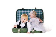 Menino e uma menina que senta-se em uma mala de viagem Foto de Stock