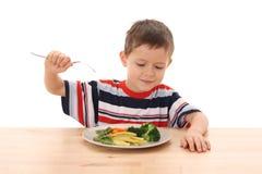 Menino e vegetais cozinhados foto de stock