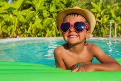 Menino em óculos de sol coração-dados forma no colchão de ar verde fotos de stock