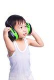 Menino em capas protetoras para as orelhas vestindo de uma camiseta interioa branca Imagem de Stock Royalty Free
