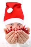 Menino em decorações do Natal da terra arrendada do chapéu de Santa fotografia de stock royalty free