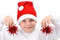Menino em decorações do Natal da terra arrendada do chapéu de Santa imagem de stock royalty free