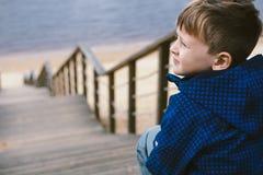 Menino em escadas perto do lago Conceito de espera fotografia de stock royalty free