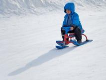 Menino em passeios do pequeno trenó do inverno na montanha imagem de stock