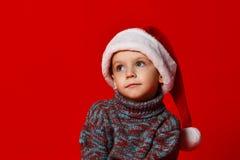 menino em sonhos do retrato do chapéu de Santa Claus dos presentes em um fundo vermelho imagens de stock