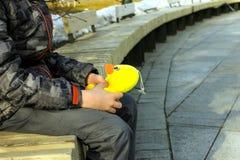 Menino em um banco com um patinho fotografia de stock royalty free