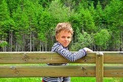 Menino em um banco de madeira Fotografia de Stock