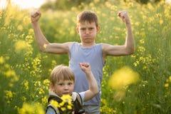 Menino em um campo amarelo da colza na noite no por do sol Fotografia de Stock Royalty Free